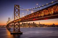 Twilight over the Oakland Bay Bridge with skyline of San Francisco beyond, California USA.