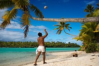 Aitutaki. Cook Island. Polynesia. South Pacific Ocean. An inhabitant of the island takes up a coconut palm tree on the beach in One Foot Island. One F...