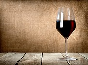 Red wine glass on the wooden table.