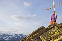 Young woman standing at the cross on a summit in the mountains, See, Tyrol, Austria
