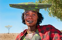 Namibia Africa Northern Desert colorful Herero tribe woman in plaid dress and hat and traditional costume in Tomakas in Puros Conservancy remote villa...
