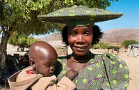 Namibia Africa Northern Desert colorful Herero tribe women in plaid dress and hat with child and traditional costume in Tomakas in Puros Conservancy r...