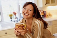 Smiling Woman with Cup in Kitchen