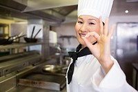 Portrait of a smiling female cook gesturing okay sign
