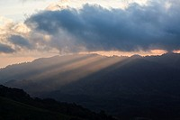Sunrise and light beams over forested hillsides. Doi Pha Hom Pok National Park. Thailand.