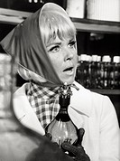 Doris Day acting. The American actress and singer Doris Day wearing a headscarf holding a bottle in her hand looking at someone with perplexity in a s...