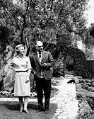 Luigi Barzini junior and Paola Gadola in the garden. Italian journalist and politician Luigi Barzini junior walking with his wife Paola Gadola in the ...