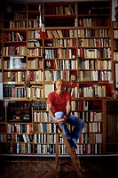 Mino Milani sitting before his library. Journalist and cartoonist Mino Milani poses in casual clothes on a small ladder in front of the furnished libr...