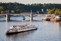 Boat on Vltava River and Manes Bridge, Prague, Czech Republic.