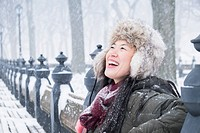 Asian woman sitting on park bench in snow