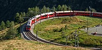 Bernina Express at Alp Gruem, with the Valposchiavo in the background, Engadin, Switzerland.