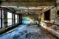 An abandoned office in an old building showing peeling paint on walls and ceiling. Birmingham, Alabama, USA