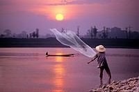 cast net fishing on Mekong River at sunset in northeastern Thailand, Southeast Asia.
