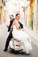 Bridal couple on their journey with a Vespa