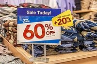 Sign indicates discounts on clothing in retail clothing bargain store.