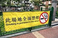 """Hong Kong, China, Asia. Hong Kong Kowloon. Large yellow bilingual banner in english and chinese at the entrance to a small urban park advising that """"""""..."""