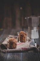 Two glasses of Granita al caffe, kitchen towel and espresso can on dark wood