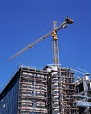 Gebaeude mit Baugeruest, Malergeruest, eingeruestete Hausfassade, Bauarbeiten, Baustelle, Baukran, Konstruktionskran, Kranausleger building with scaff...