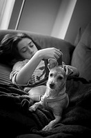 Teenage girl with her dog on the couch at home. Peniscola, Castellón, Valencia, Spain.