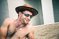 Happy shirtless man in hat and sunglasses relaxing outdoors.