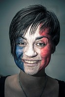 Portrait of happy woman with flag of France painted on face.