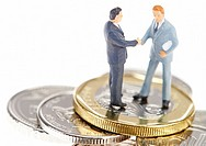 Two businessman shaking hands on Singapore coins.
