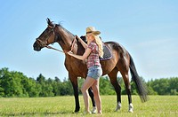 Young cowgirl with a polish arabian horse standing on a meadow.