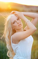 Portrait of a young woman in cornfield at sunset.