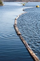 log boom barrier floating on water, Finland.