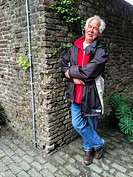 Tilburg, Netherlands. Elder vicar of pastor leaning on a century old wall in a museum´s garden.