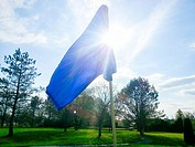 The flag atop the pin on the green of a golf course in Southern Ontario, Canada on a spring day.