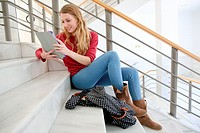 Young female student with digital tablet at campus