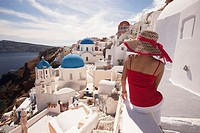 Woman in front of the blue domed church in Oia town looking at Caldera, Santorini, Cyclades Islands, Greek Islands, Greece, Europe.