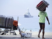Workers sets up chais to rent by tourists at beach, naval ship in the background, Ipanema, Rio De Janerio, Brazil.