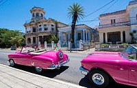 Havana Cuba pink classic 1950s auto in beautiful neighborhood of Habana parked.