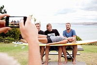 Young woman photographing surfer friends with smartphone