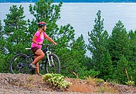 A woman mountain biking on Osprey Point in Ponderosa State Park above Payette Lake near the city of McCall in the Salmon River Mountains of central Id...