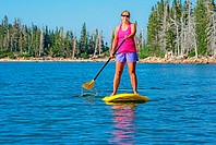 A woman riding the Standup Paddle Board at Lake Cleveland on Mount Harrison high on in the Albion Mountains in southern Idaho.