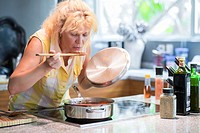 A woman is taking a taste of a red tomato sauce on a wooden spoon in her kitchen.
