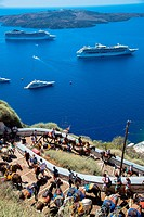 donkeys with tourists on their back on their way up from the harbour and passenger ships seen from Santorini island in Greece