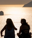 girlfriends enjoy seaview from milos greece at sunset