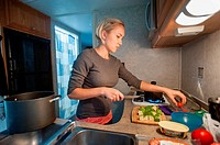 Woman cooking in RV kitchen.