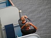 Two men with binoculars on a ships balcony.