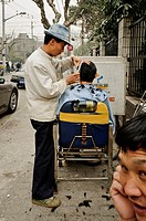 A barber in the street, Shanghai, China, Asia.
