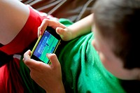 An 8 year old boy sitting on a sofa and playing a game on an ipod.