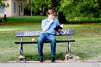 Young man sitting on a park bench .