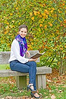 Woman on a park bench with book. Woman in white blouse with blue scarf and blue jeans is sitting on bench in a park.