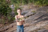 Teenage boy holding up smallmouth bass fish, Lake Superior, Au Train Bay, Michigan, USA