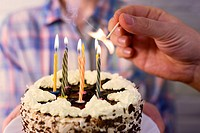 male hand lights the candles on the birthday cake.