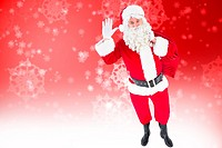 Composite image of santa holding a sack and waving